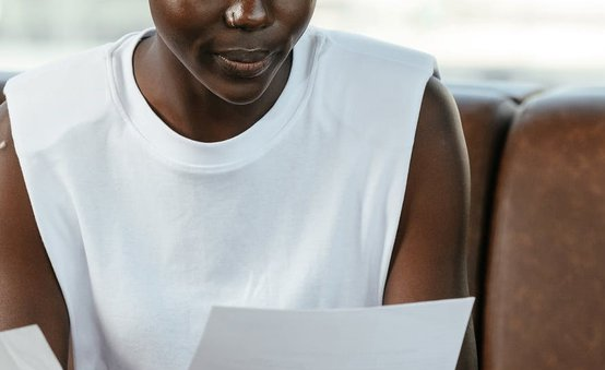 A Black woman reading a piece of paper